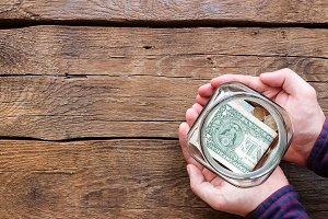 man holding glass jar of fundraising