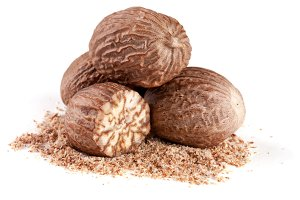 four nutmeg and powder isolated on white background