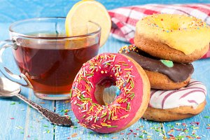 pile of glazed donuts with a cup of tea on a blue wooden background