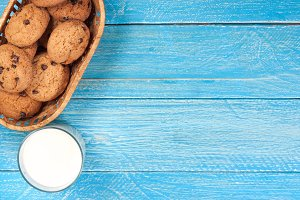 glass of milk with oatmeal cookies on a blue wooden background with copy space for your text. Top view
