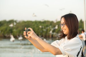 Asian woman using a camera phone.