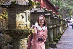 woman standing near a stone lantern.
