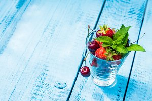 Glass with ripe summer berries