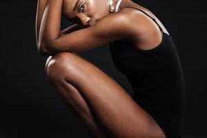 Beautiful african woman in bodysuit posing in studio