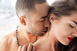 Close-up portrait of young man kissing woman's neck
