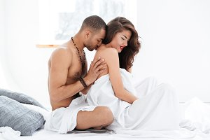 Portrait of an attractive young couple caressing laying in bed