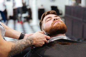 Barber shaving beard of his client