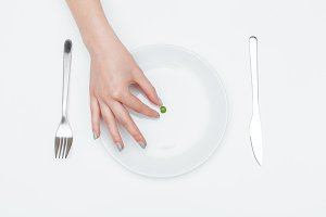One green pea on the plate taken by woman hand