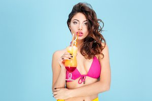 Beautiful young woman drinking cocktail wearing swimsuit
