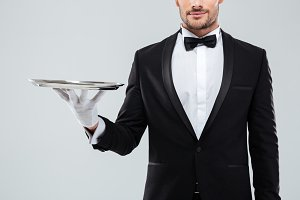 Closeup of waiter in tuxedo and gloves holding silver tray