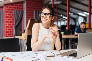 Smiling pretty young business woman in glasses sitting on workplace