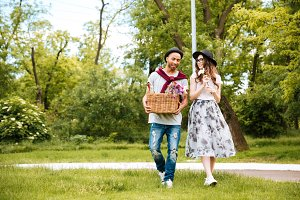 Beautiful couple with drinks and food in basket in park