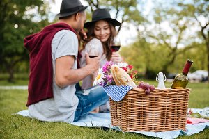 Basket with food and drinks standing near couple in park