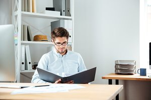 Concentrated young businessman working with documents in folder