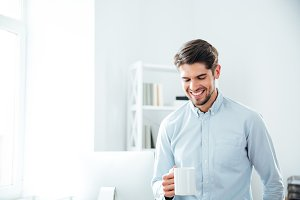 Cheerful young businessman drinking coffee in office