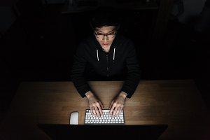 Top view of man using laptop in dark room