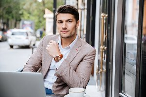 Serious businessman using modern laptop in coffee shop