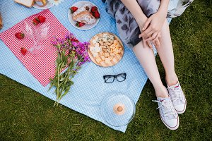 Legs of young woman sitting on blanket and having picnic
