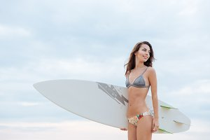 Smiling woman surfer in swimwear with white surfboard