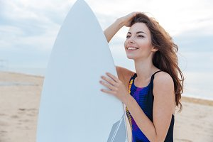 Beautiful surfer teen girl standing with surfboard