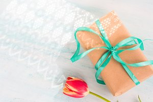 Gift box with green ribbon pastel background. Holiday present