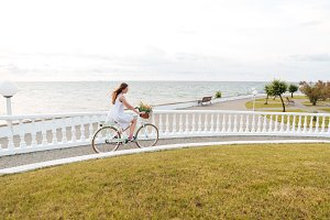 Woman riding bicycle on promenade in summer