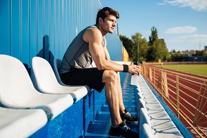 Young handsome male athlete resting after workout