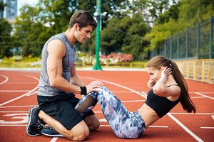 Young beautiful couple doing exercises at the stadium