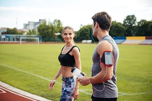 Happy young sportive man and woman talking on stadium