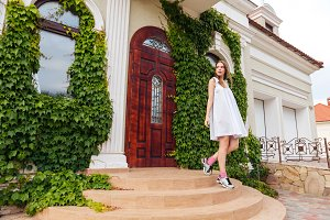 Attractive girl in white dress goes down the stairs outdoors