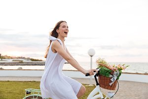 Cheerful woman laughing and riding bicycle in summer