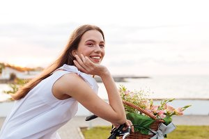Smiling woman riding bicycle with flower basket in summer