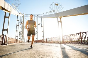 Sports man running along big modern bridge at sunset light