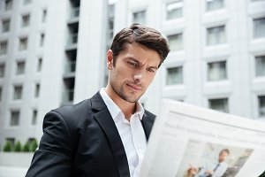 Businessman reading newspaper in the city