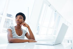 Portrait of a serious thoughtful businesswoman using laptop in office