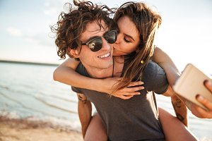 Young happy couple kissing and making selfie at the beach