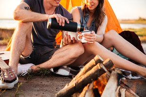 Cropped image of a couple drinking tea at the bonfire