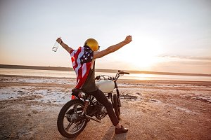 Man in american flag cape with hands up in air