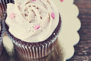 Chocolate cupcakes decorated with cream rose hearts toning
