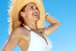 Smiling woman in straw hat at sandy beach looking into distance