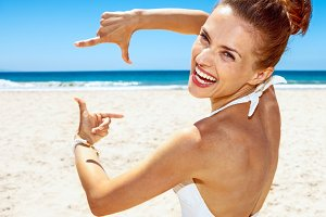 Smiling woman in swimsuit at sandy beach framing with hands