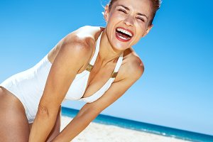 Smiling woman in white swimsuit at sandy beach on a sunny day