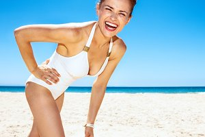 Portrait of happy woman in white swimsuit at sandy beach