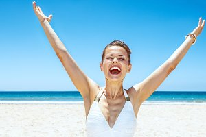 Happy woman in swimsuit at sandy beach on sunny day rejoicing