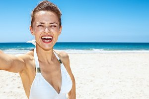Smiling woman in white swimsuit taking selfie at sandy beach