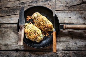 Two roasted chicken rolls lying on grill pan
