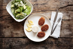 Overhead view of fish croquettes with fresh salad