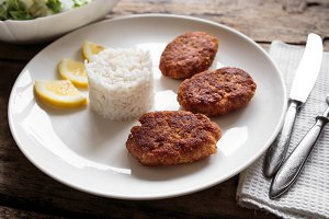 Three fish cutlet on white plate with rice