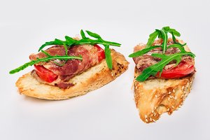 Two bruschettes with arugula in fillet of tuna and green sauce