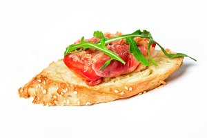 Bruschetta with serrano ham, cheese and arugula